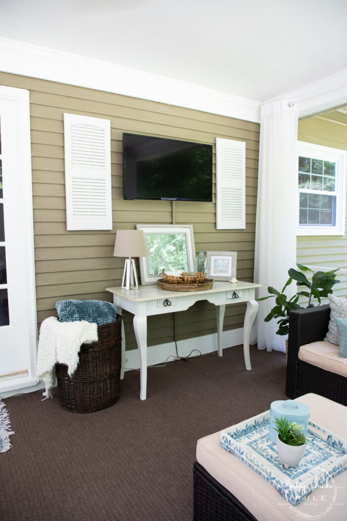 screened porch wall with tv and console table with white shutters