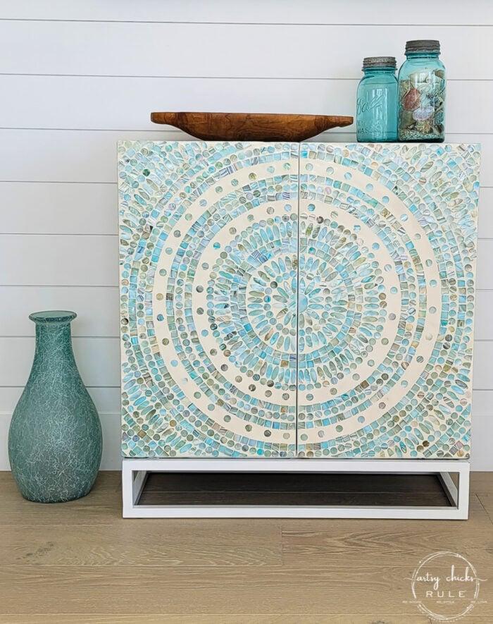 aqua mosaic tile cabinet with blue jars and wood bowl