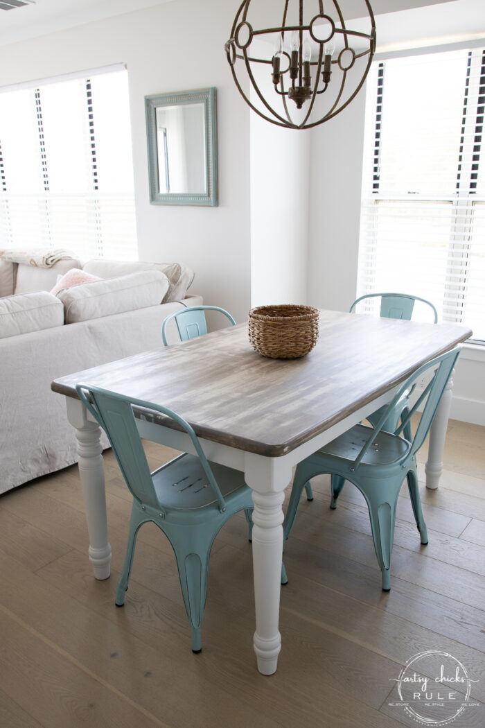 weathered driftwood table with blue metal chairs