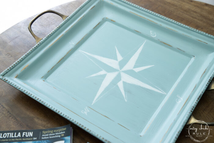 sideview of aqua tray with white compass rose up close