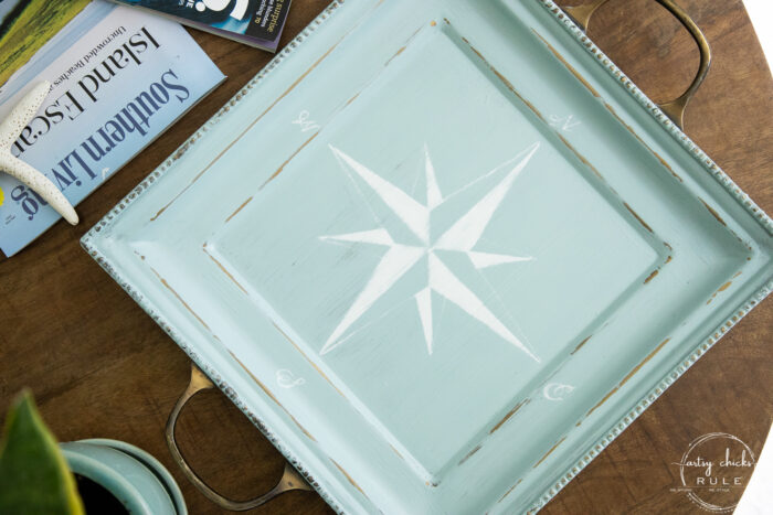 top view of blue tray with white compass rose on wood table