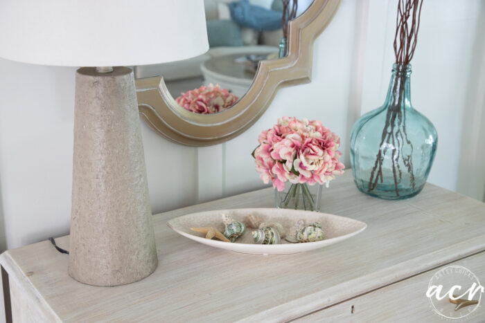 top of dresser with seashells in dish, pink flowers, blue vase and new lamp