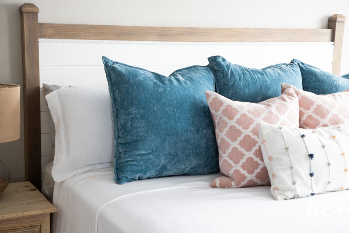 headboard on wall with bedding blue pillows, pink pillows