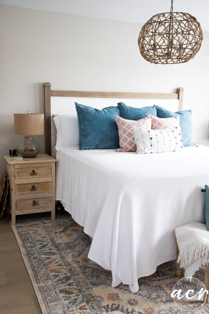 colorful pillows on white bed on colorful rug