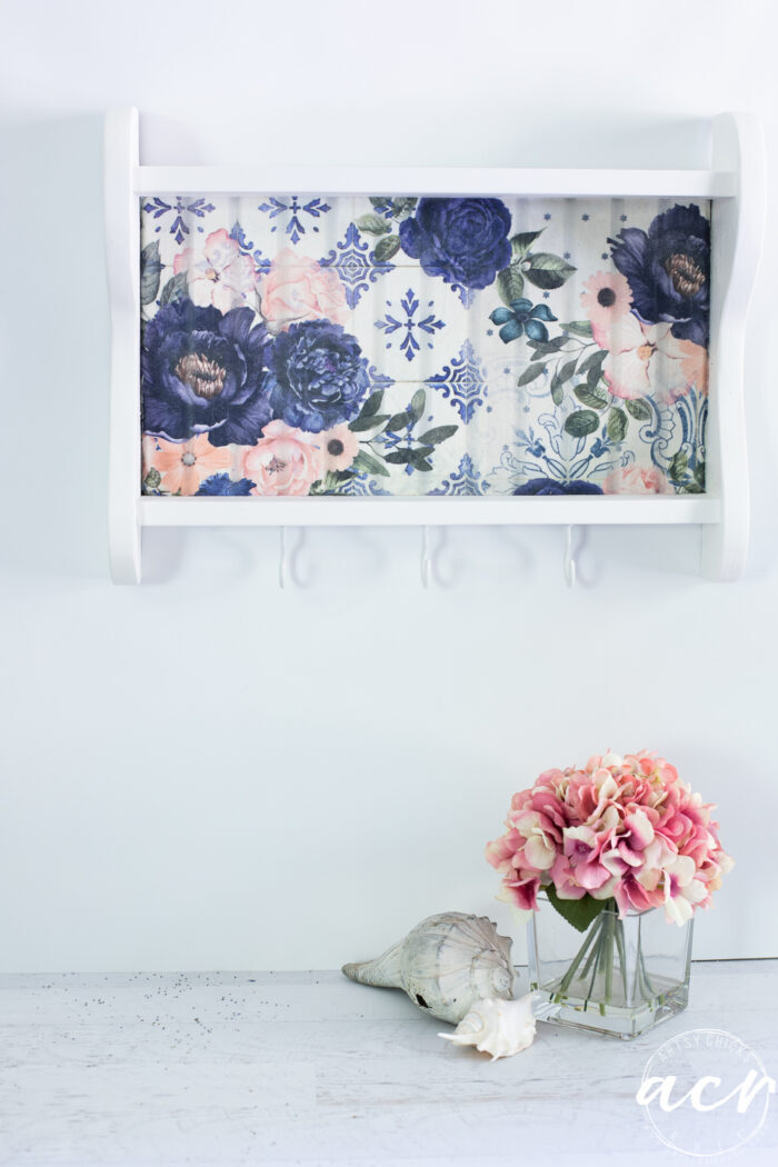 white shelf with blue flowers hanging on wall