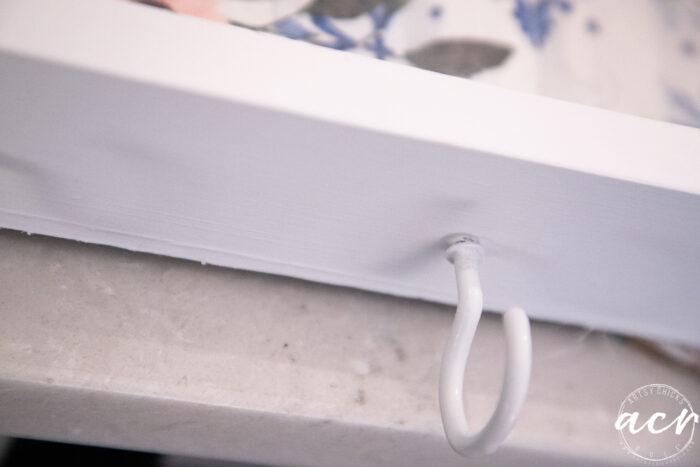 up close of white hook on bottom of shelf