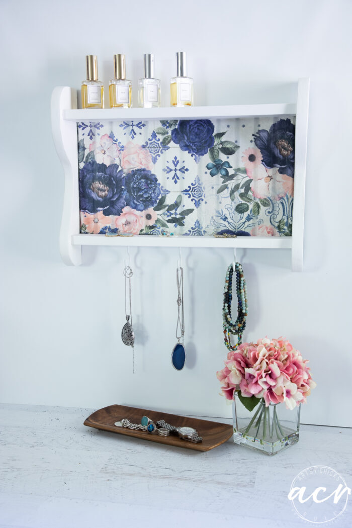 white shelf with blue flowers styled with perfume bottles and jewelry