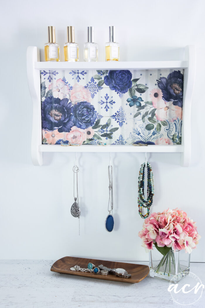 blue floral shelf hanging on wall with jewelry