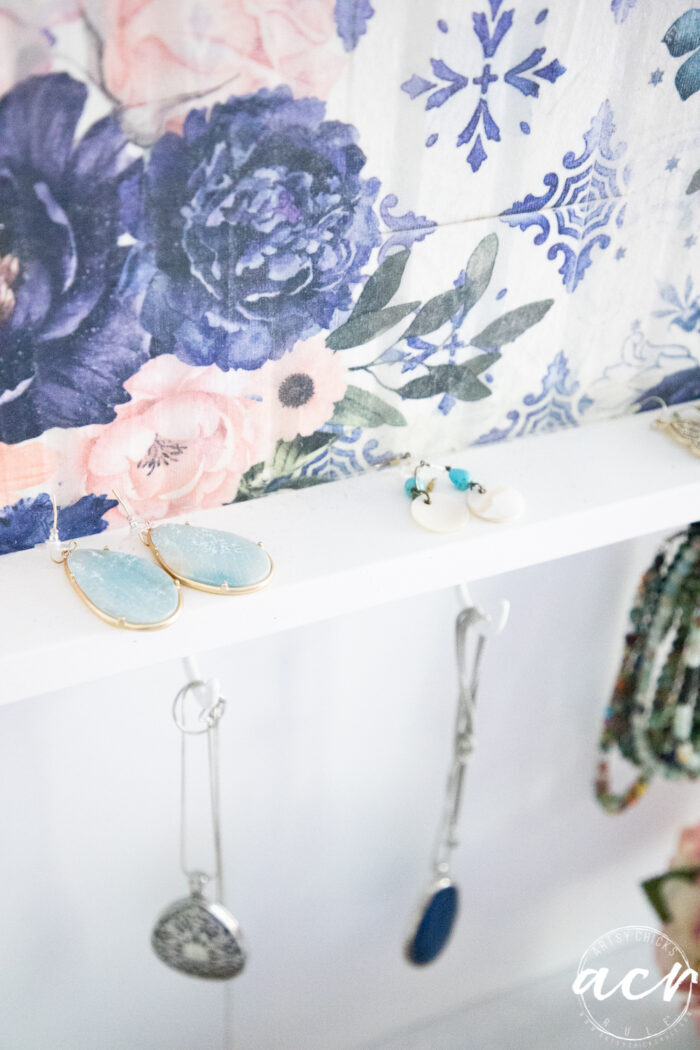 up close of blue floral shelf showing earrings on shelf and necklaces hanging