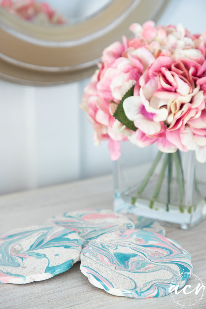 pink flowers in vase with blue and pink coasters