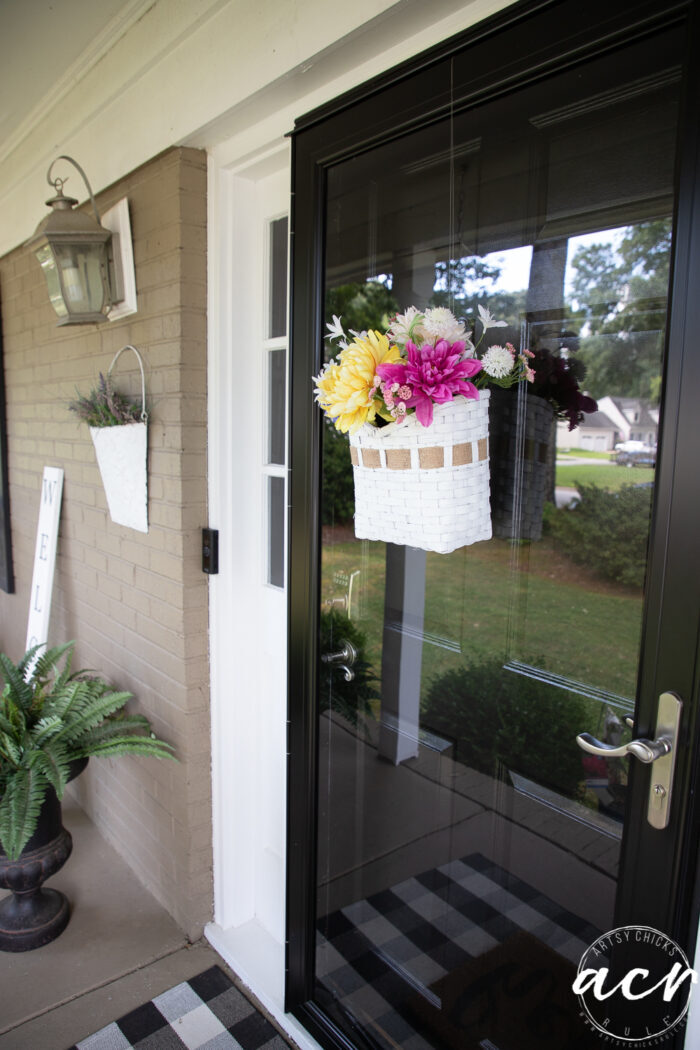 black and white porch with colorful basket on door
