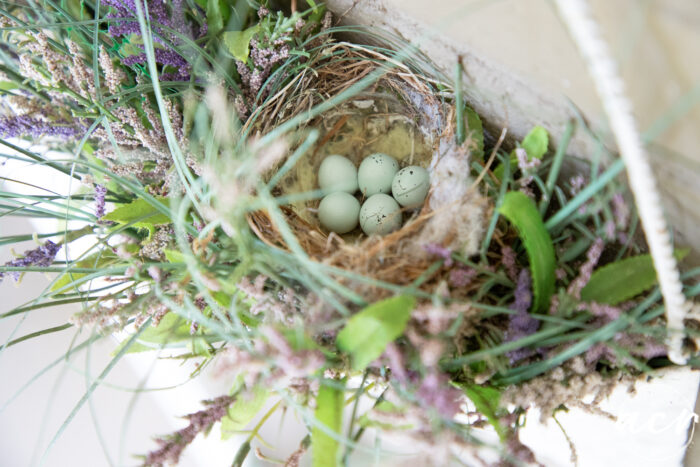 top view of hanging metal basket with bird's nest and baby blue speckled eggs