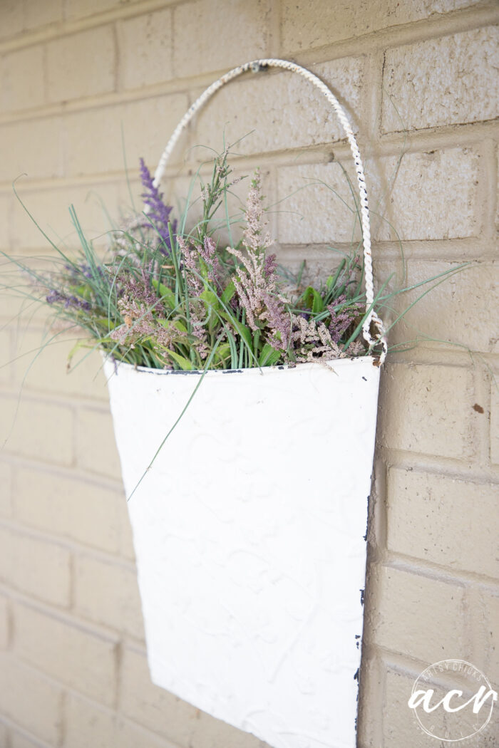 white metal half basket on brick wall with flowers in side