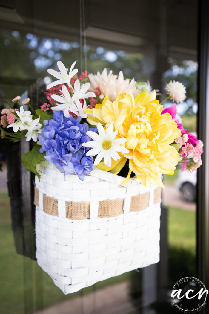 yellow and purple flowers in white basket