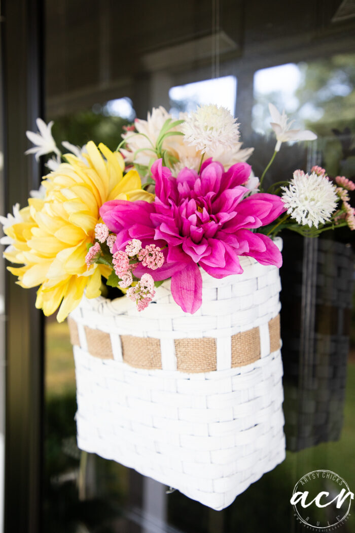 hot pink and yellow flowers in white basket