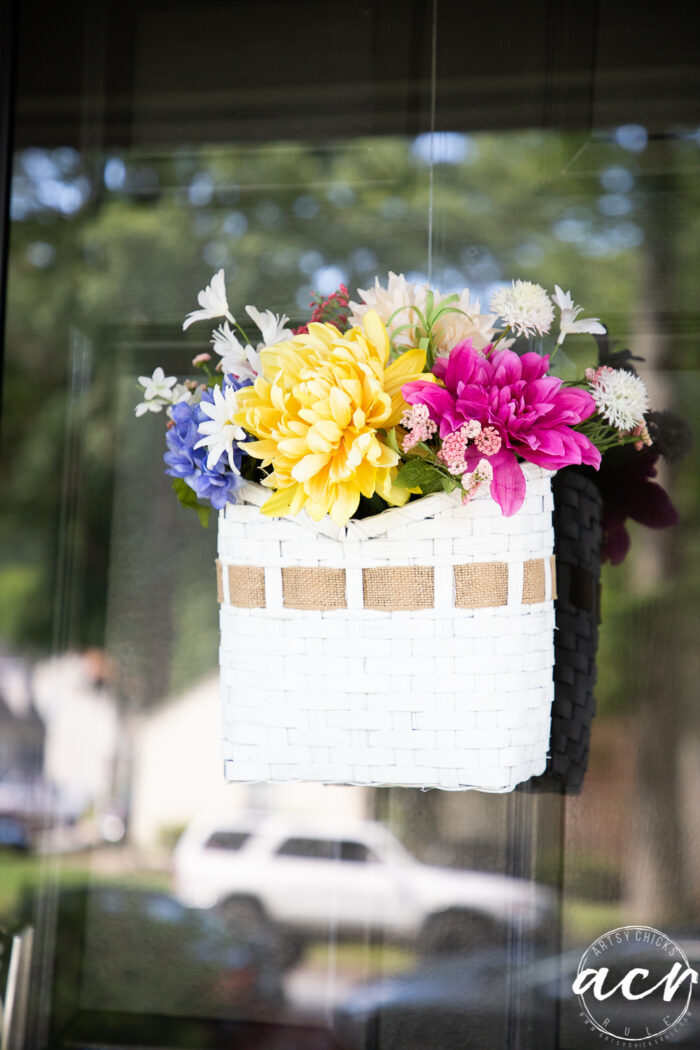 front view of basket with burlap ribbon and colorful flowers