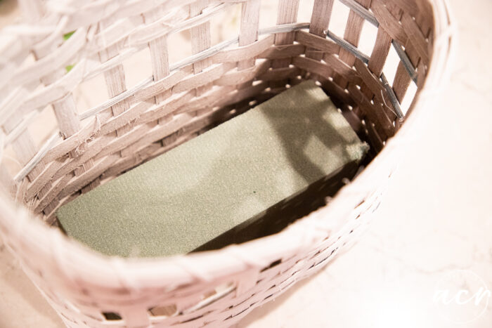 adding florist foam to the bottom of the basket
