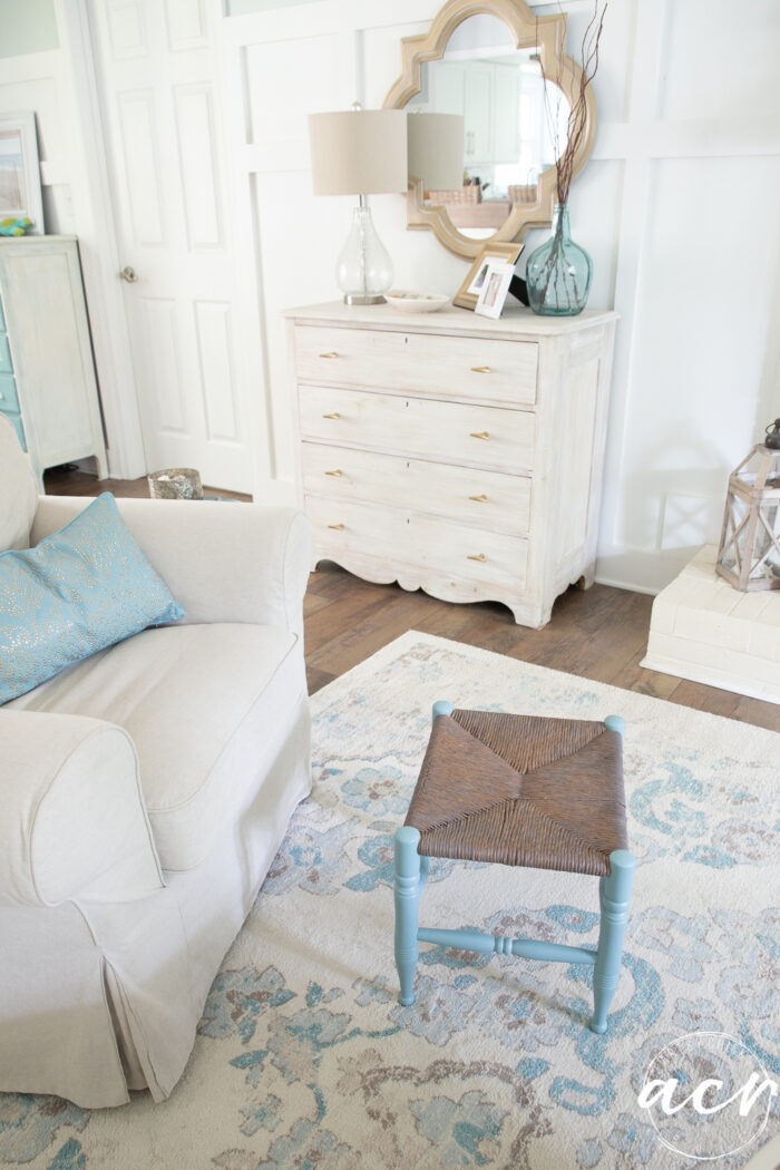 coastal style home with white walls blue footstool and gold mirror