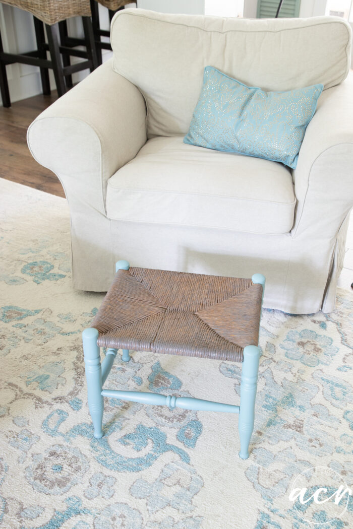 footstool in front of tan chair