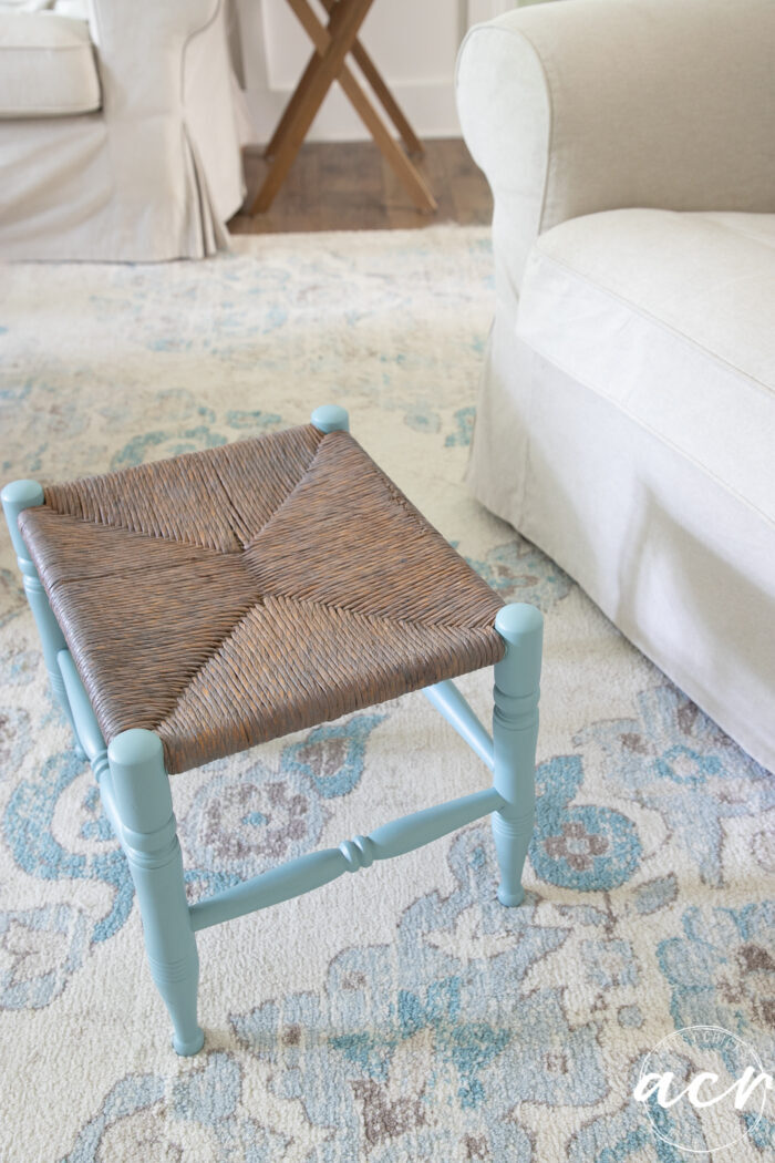 blue and brown colored footstool on cream and blue rug