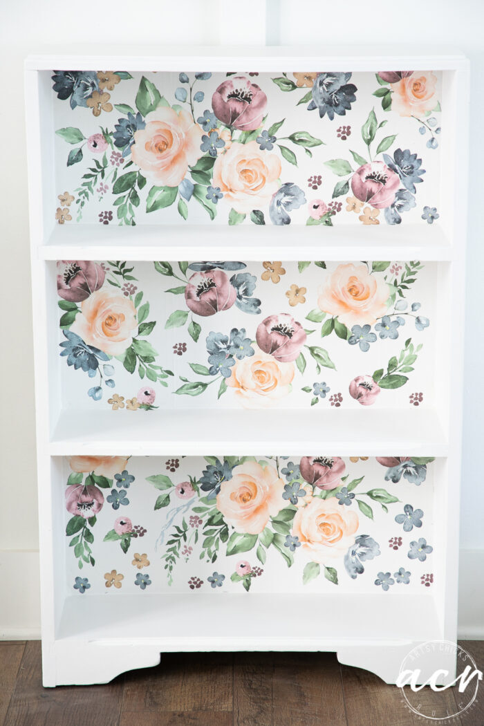 small white bookcase with colorful floral backing