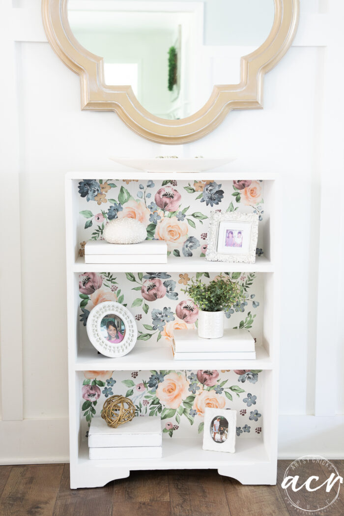 white bookcase with floral backing, gold mirror, styled shelves