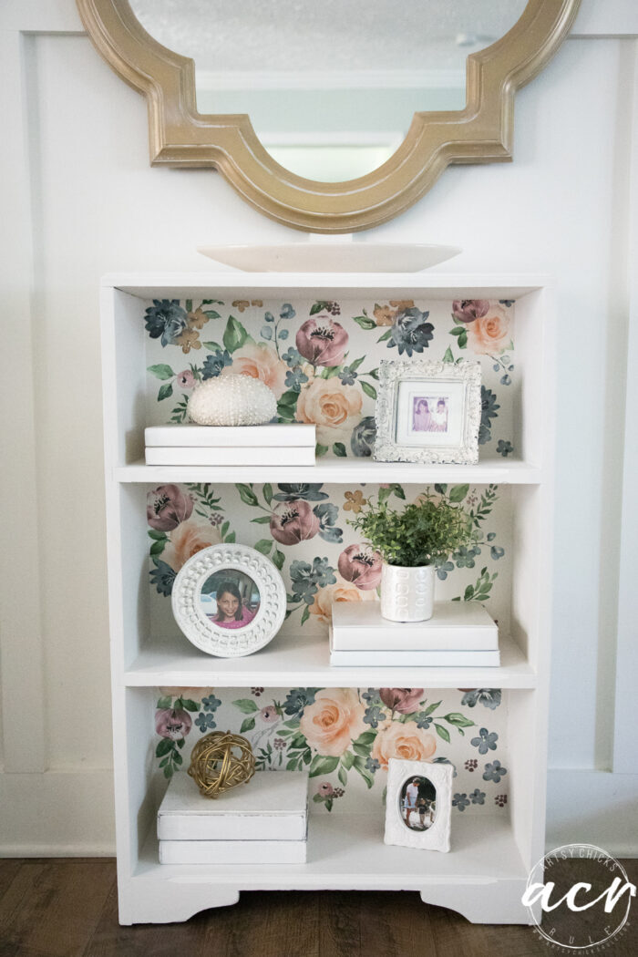 white bookcase styled with gold mirror over top