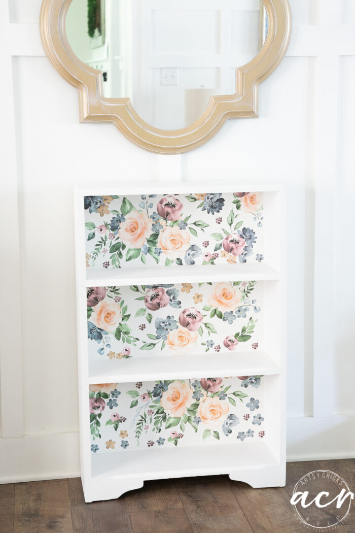 floral and white bookcase with white wall and gold mirror