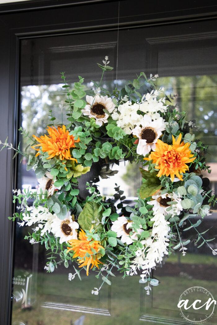 orange flowers white sunflowers on green wreath hanging on door