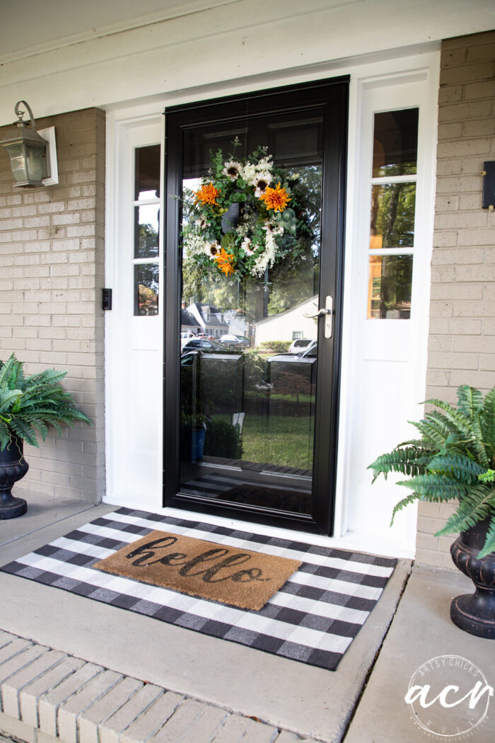 front porch with black door and fall wreath, green ferns
