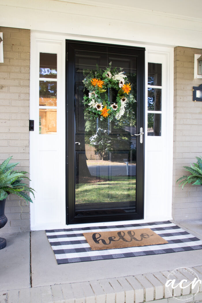 black front door with fall wreath and hello mat