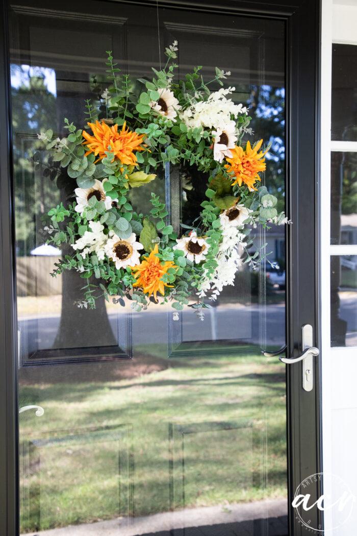glass storm door with fall wreath