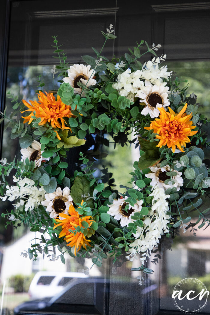 green wreath on door with orange flowers and white sunflowers