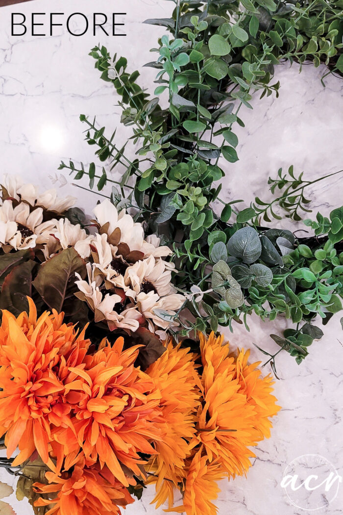 green wreath before with bunches of orange and cream flowers beside it