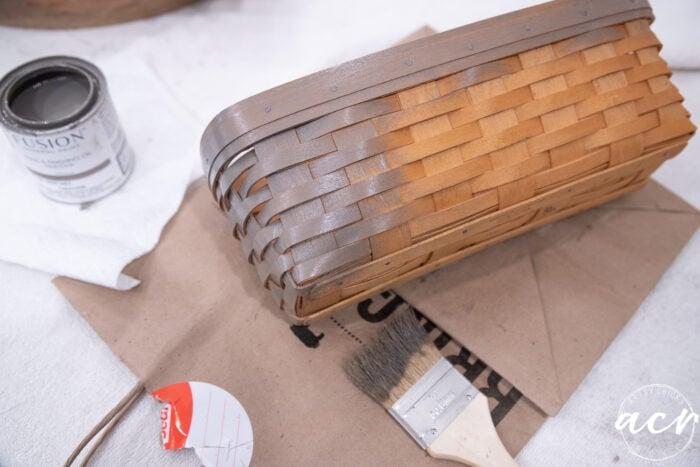 applying driftwood stain to the orange basket