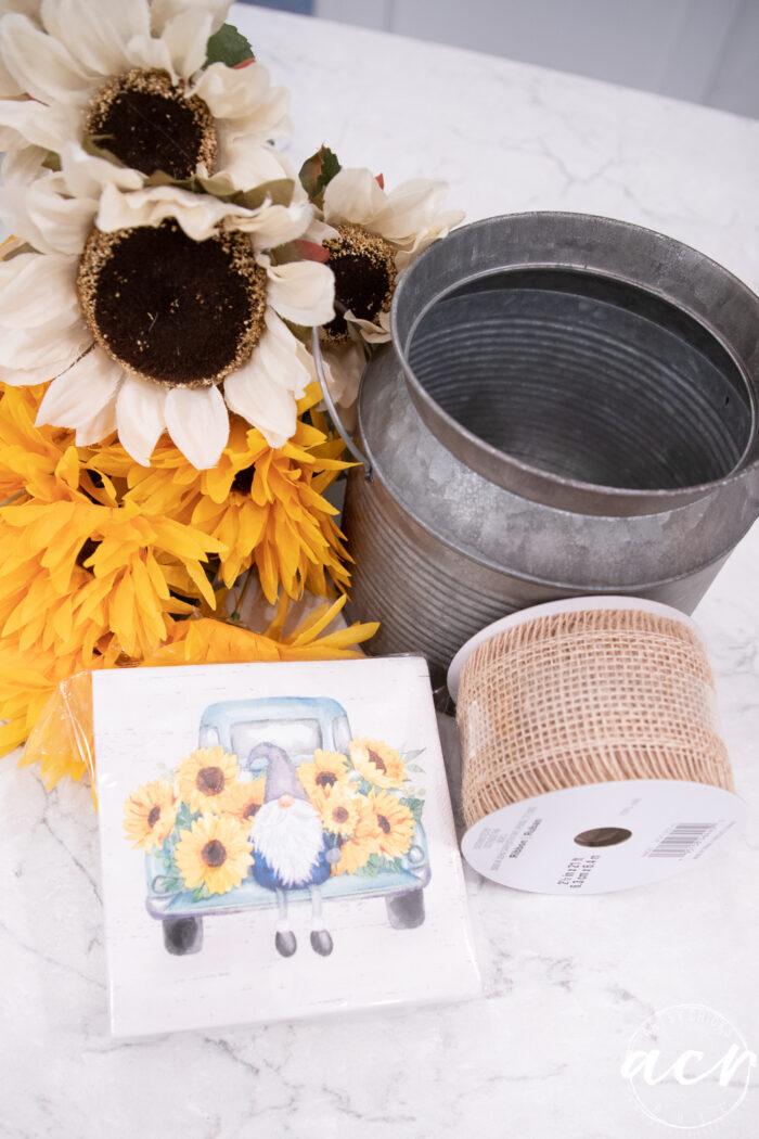 tin, burlap ribbon, knome napkin, yellow and white sunflowers