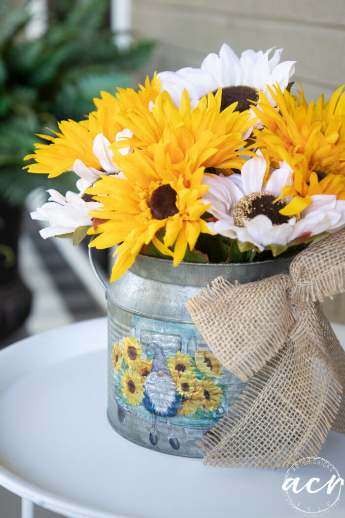 finished yellow and white sunflower arrangement inside tin on white table