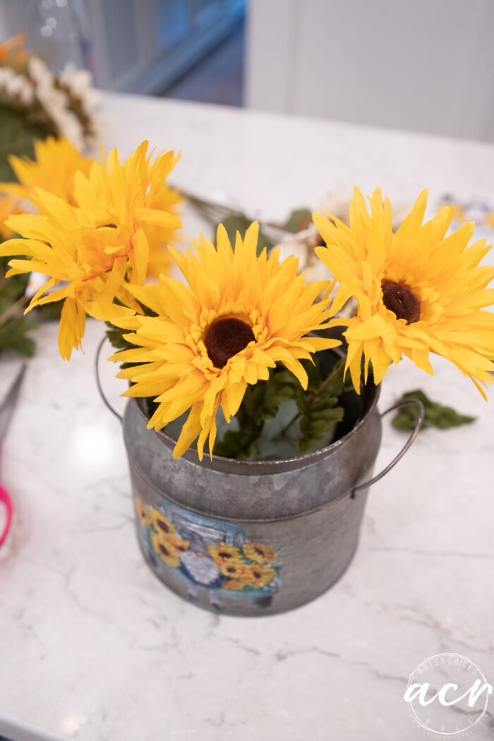 adding the yellow sunflowers to the tin