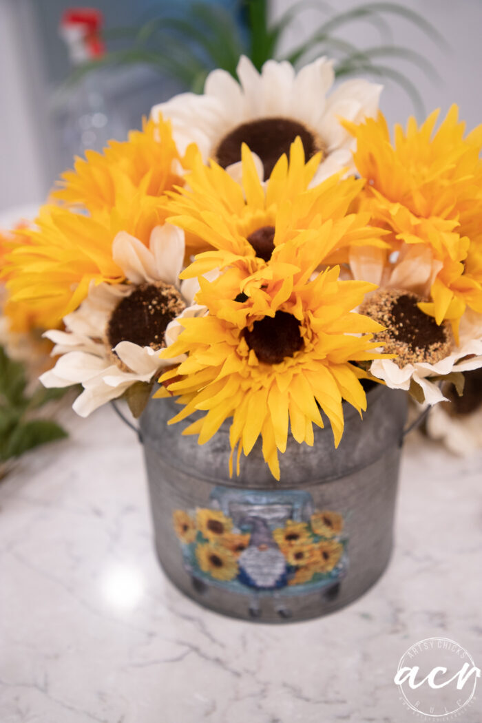 yellow and white sunflowers in tin on counter