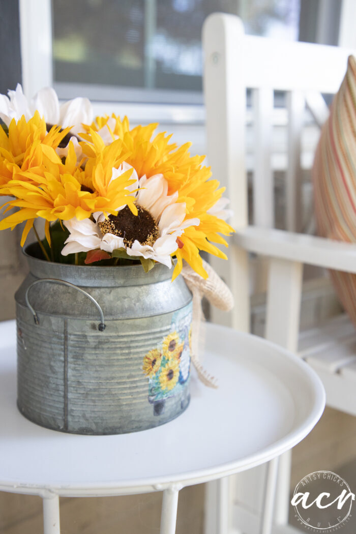 flowers in tin on white table on porch