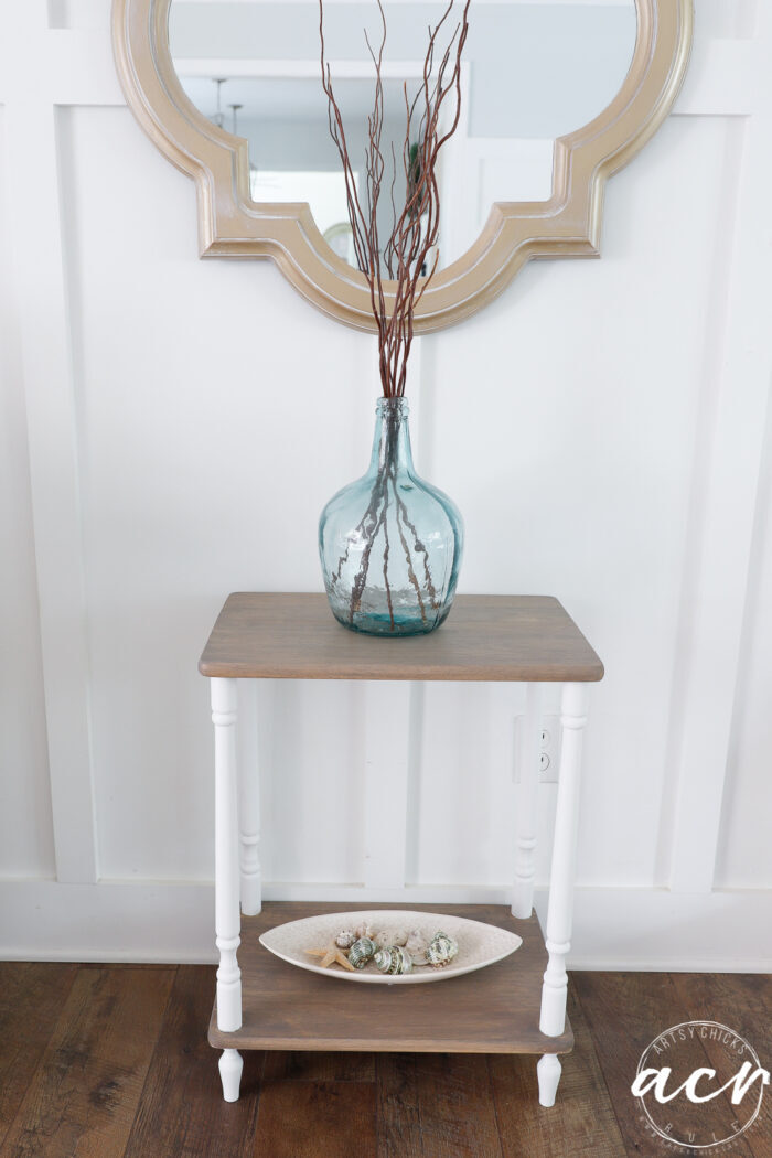 driftwood and white table with blue vase and dish with seashells on bottom