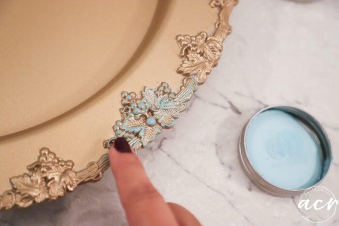 finger applying patina wax to gold tray