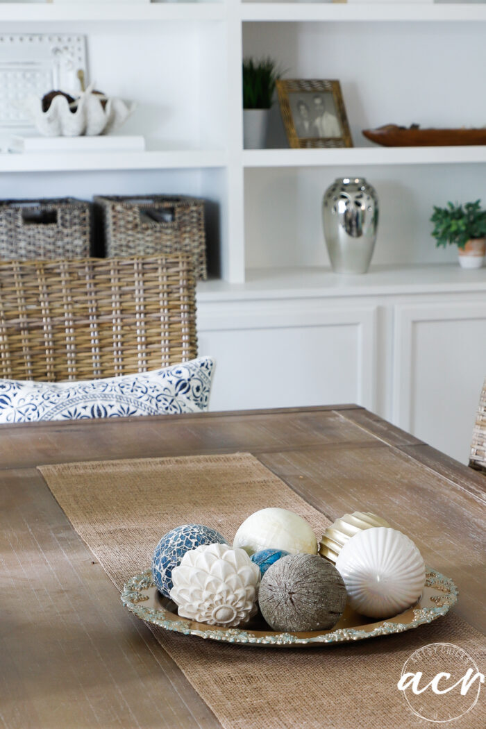 dining table with decorative balls on gold patina'd tray