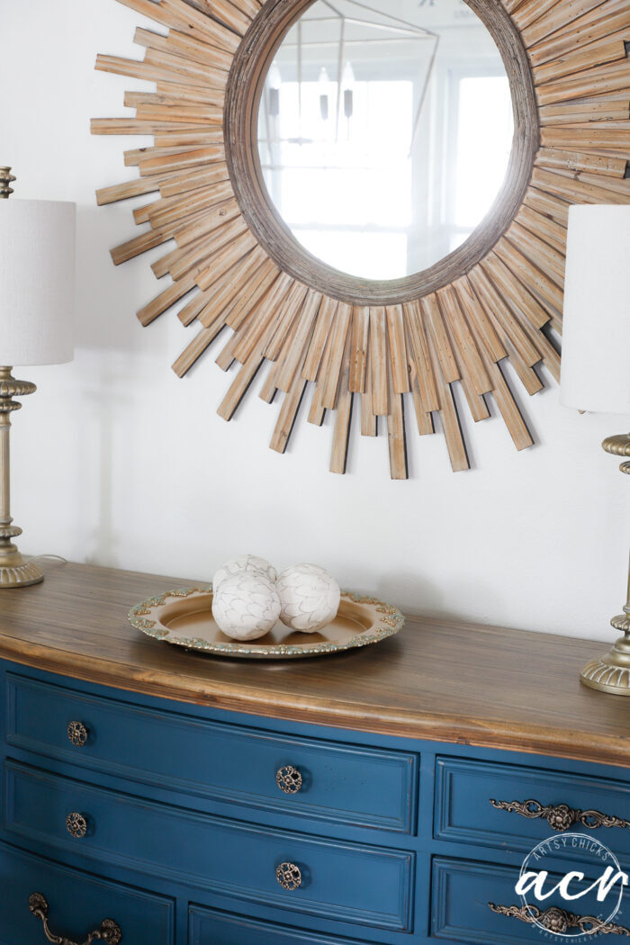 blue dresser with wood starburst mirror and gold tray
